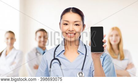 medicine, profession and healthcare concept - happy smiling asian female doctor or nurse in blue uniform with stethoscope showing smartphone with medical team at hospital on background