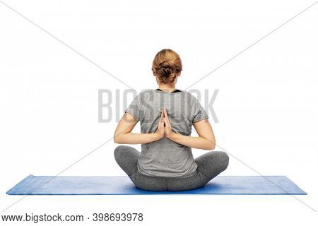 yoga, sport and healthy lifestyle concept - woman doing reverse prayer pose on mat