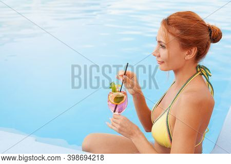 Beautiful Happy Woman Smiling, Looking Away Dreamily Enjoying Her Cocktail At The Swimming Pool. Att