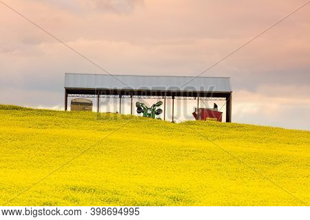 Farming Shed With Machinery And Equipment  Sits Among Golden Canola Fields