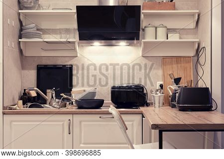 The Kitchen Is Cluttered With Dishes, Appliances And Items. Dirty Plates And Pans In The Kitchen Sin