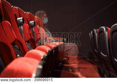 A Viewer In A Medical Mask Watching A Movie In An Empty Cinema Hall, Transparent Concept. Problems W