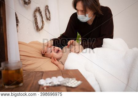 The Child At Home Is Sick, Screaming And Suffering. Dad In A Mask Checks His Daughters Temperature.