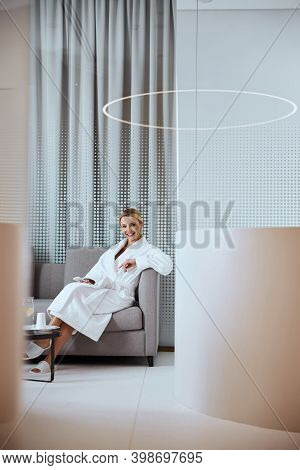 Woman With A Cellphone Sitting In The Foyer