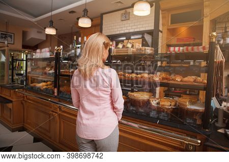 Rear View Shot Of A Female Customer Examining Delicious Pastry For Sale On Bakery Display