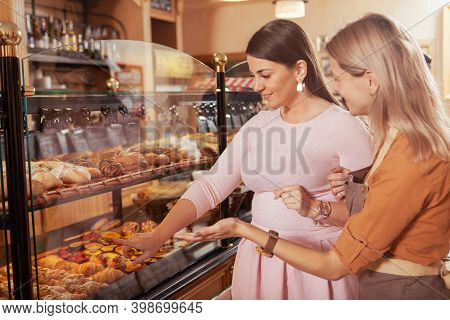 Beautiful Plus Size Woman Buying Pastry From A Female Baker. Mature Female Baker Helping Her Custome