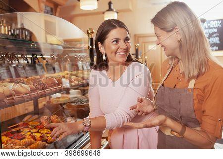 Happy Beautiful Plus Size Woman Talking To A Baker, Choosing Pastry To Buy. Female Entrepreneur Talk