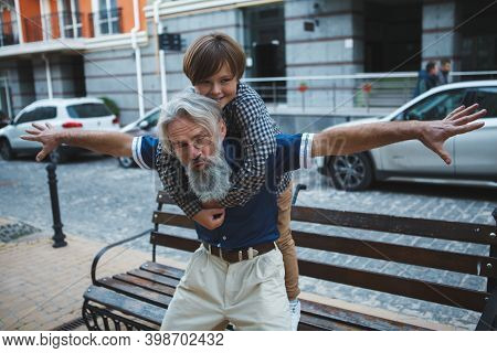 Senior Man Piggybacking His Young Grandson On City Streets