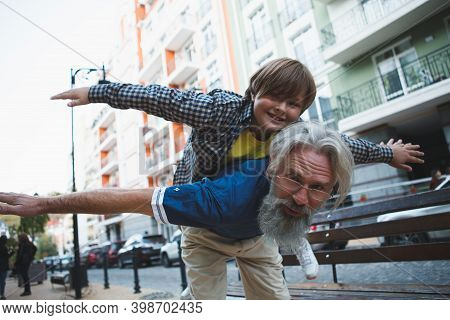 Low Angle Shot Of A Happy Grandpa Piggybacking His Grandson On City Street