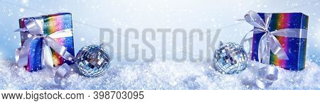 Blue Christmas Banner With Rainbow Colors Gift Box And Disco Ball In Snowdrift, Copy Space