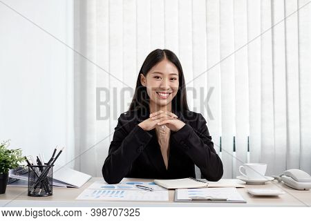 Asian Businesswomen Sit At Their Desks And Calculate Financial Graphs Showing Results About Their In