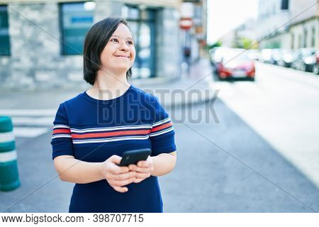 Beautiful brunette woman with down syndrome at the town on a sunny day using smartphone