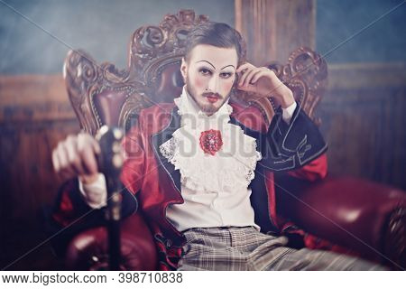 Art, history and fashion. Sophisticated young man with make-up and clothes in the style of the Rococo and Baroque eras in a rich vintage interior.