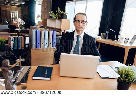 Adult Confident Man In Suit Is Sitting At Table In Office. Attorney In Business Suit Is Sitting At L