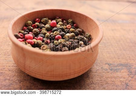 Various Species Multicolored Peppers In Wooden Bowl On Wood Table Background. Top View, Copy Space