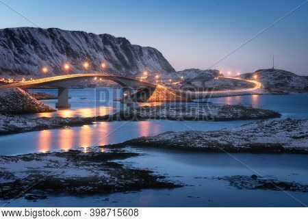 Bridge With Illumination, Snow Covered Mountains, Village And Blue Sky With Reflection In Water. Nig