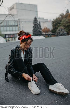 Beautiful Young Woman Sits On Pavement Of City Street And Ties Shoelaces On Her Sneakers.