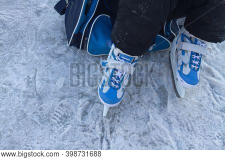 A Child In White, Blue Skates Sits On The Ice And Puts On Skates Before Skating On The River In Wint