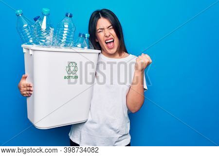 Young beautiful woman recycling plastic bottles on wastebasket to care environment screaming proud, celebrating victory and success very excited with raised arm