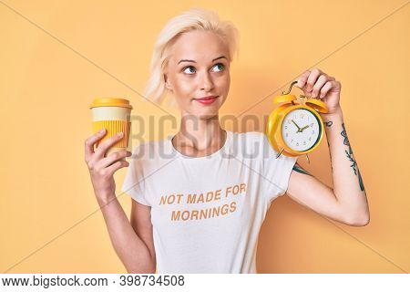 Young blonde woman with tattoo holding alarm clock and take away cup of coffee smiling looking to the side and staring away thinking.