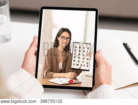 Female Teacher Teaching Online From Tablet Computer Screen Talking To Distant Student Indoors, Point