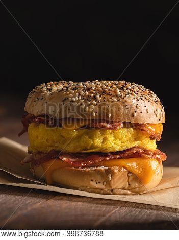 Bagel Breakfast Sandwich With Bacon, Egg And Cheddar Cheese On A Rustic Wooden Table With Copy Space