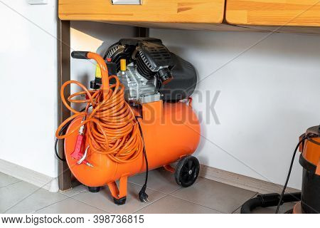 Orange Small Portable Industrial Power Air Compressor With Coil Hose And Pneumatic Gun At Home Wareh