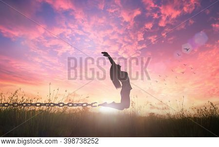 Individual Human Right Day Concept: Silhouette Of A Woman Jumping And Broken Chains At Orange Meadow