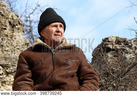 Portrait Of Elderly Man In Leather Coat And Knitted Hat In A Mountains On Blue Sky Background. Conce