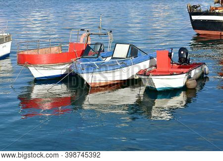Camariñas, Spain. November 28, 2020. Colorful Fishing Boats Moored In A Harbor With Water Reflection