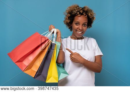 Shopping Woman Holding Shopping Bags Looking At Camera Smiling And Pointing On Her Purchases.