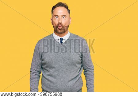 Handsome middle age man wearing business clothes making fish face with lips, crazy and comical gesture. funny expression.