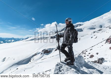 A Man With Skis Stands High In The Mountains Enjoying The Scenery. Go Downhill Skiing, Extreme Relax
