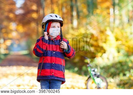 Little Kid Boy Wearing Medical Mask Put Safety Helmet On Head For Biking. In Autumn Forest Park With