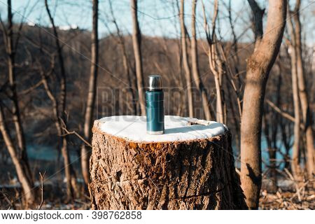 Thermos Standing On A Tree Stump Covered With Snow.