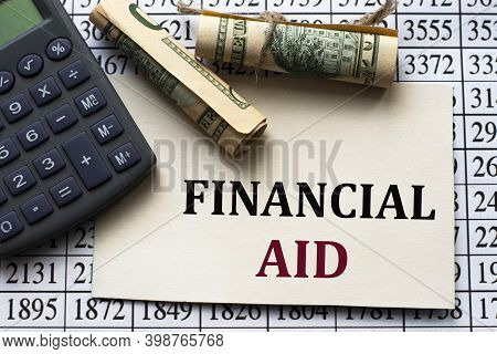 Financial Aid - Words On White Paper Against The Background Of A Table Of Numbers With A Calculator