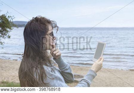Reading A E-book On The Beach. Holding A E-book