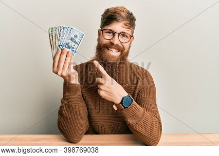 Young irish redhead man holding dollars sitting on the table smiling happy pointing with hand and finger