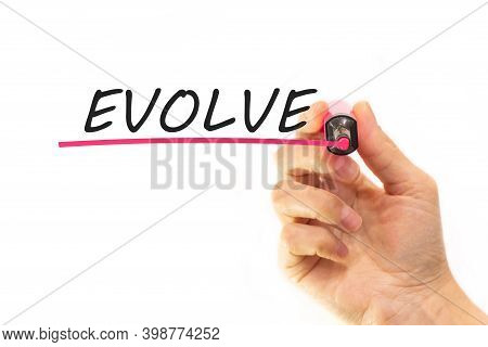 The Hand Writes The Word Evolve With A Marker On A White Background. Business Concept
