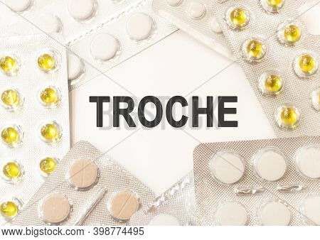 Text Troche On White Background. There Are Various Pills And Vitamins Around. Medicine Concept