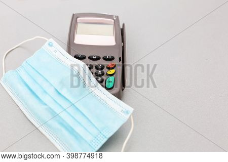 A Pos With Medical Mask Waiting For A Contactless Nfc Payment Of Groceries On A Gray Background. Nfc