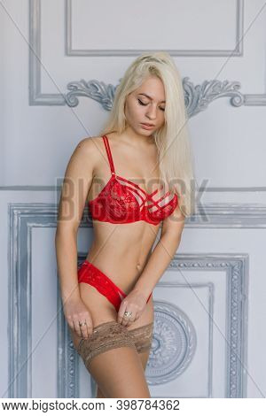 Sexy Fashion Model With Blond Hair, Posing In Bedroom, Wearing Red Lingerie