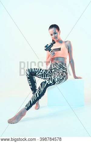 Percussion Massager, Athletic Young Brunette Female Showing Handheld Massaging Gun Sitting On Cube I