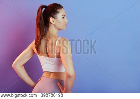 Fitness Young Pretty Woman In Gray Leggings And White Tank Top Posing Backwards With Hands On Hips,