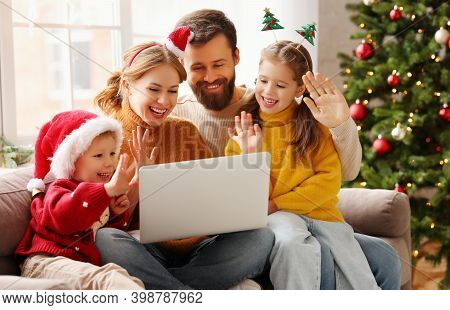 Happy Family Cheerful Parents And Joyful Children Make A Video Call To Relatives On  Holiday Near Th