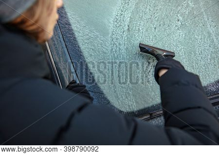 Woman Clean Snow From Windshild In Winter. Snow Removing From Car Window