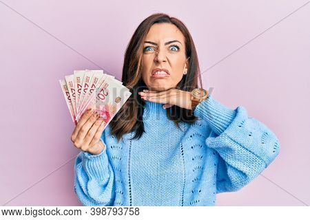 Young brunette woman holding 20 israel shekels banknotes cutting throat with hand as knife, threaten aggression with furious violence