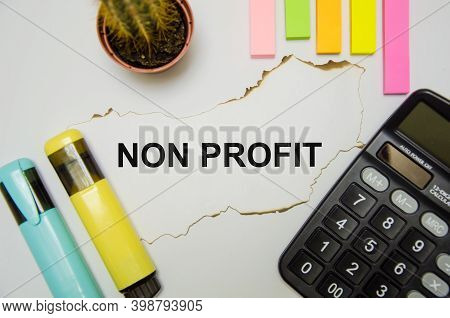 The Word Non Profit Written On A White Sheet Of Paper Which Lies On A White Background There Are Sti