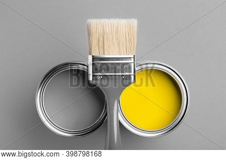 Two Cans Of Yellow And Gray Paint With Gray Brush On Gray Background. Top View, Repair Concept.