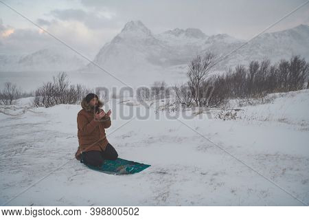 Muslim traveler praying in cold snowy winter day